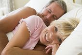 Couples Lying In Bed Together Smiling