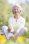 stock photo of woman glamour  - Woman sat in a field holding several buttercups - JPG