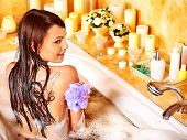 Young woman using bath sponge in bathtub.