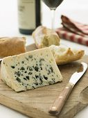Wedge Of Roquefort Cheese With Rustic Baguette And Red Wine
