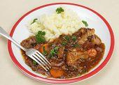 Caldeirada de rabo de boi, um prato muito antigo britânico, em um prato com purê de batata e um garfo