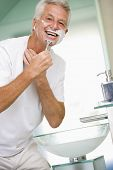 Man In Bathroom Shaving And Smiling