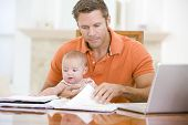 Father And Baby In Dining Room With Laptop