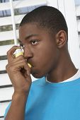image of asthma  - Young African American boy using asthma inhaler - JPG