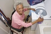 picture of laundromat  - High angle view portrait of an African American woman on wheel chair washing clothes - JPG