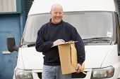 Deliveryperson Standing With Van With Clipboard And Box Smiling