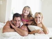 Families Lying In Bed Smiling