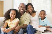 Families Sitting In Living Room Smiling