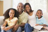 Familien sitzen im Wohnzimmer lächelnd