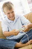 Young Boy In Living Room With Video Game Controller Smiling poster