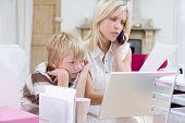 Frau über Telefon im Büro zu Hause mit Laptop, während junge wartet