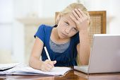 Young Girl With Laptop Doing Homework In Dining Room Looking Unhappy