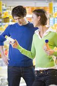 foto of grocery-shopping  - young couple choosing and buying at the supermarket