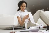 Surprised African American woman calculating her domestic expenses at home poster