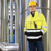 Engineer, wearing protective clothing looks kindly into the camera in front of the large stainless steel pipes in a huge boiler room