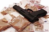 stock photo of smuggling  - a stash of drugs gun and money showing a dangerous cost to life against a white background - JPG