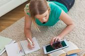 Blonde woman lying on floor using tablet to do her assignment at home in living room