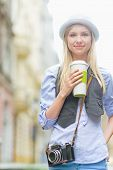 Happy Hipster Girl With Cup Of Hot Beverage On City Street