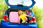 stock photo of mating  - Little three years old boy sitting in the car trunk with bags net - JPG