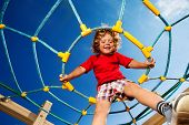 stock photo of playground  - Happy little three years old child boy sitting on the web on playground and smiling ready to jump - JPG