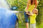 picture of soapy  - Mother and three years old son washing car with high pressure washer with boy pointing water nozzle standing in outside in the yeard parking - JPG