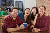 stock photo of hysterics  - Young group of hipsters laughing hysterically in a cafe - JPG