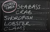stock photo of bass fish  - Blackboard sign for a seafood menu with the catch of the day - JPG