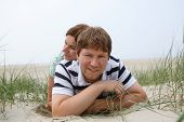 Young Happy Couple In Love Having Fun On Sand Dunes Of The Beach Of St.peter Ording