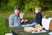 Young Father And Two Little Boys Picnicking In The Park