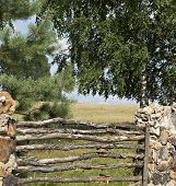 foto of old stone fence  - The old fence is made of a stone and a tree - JPG