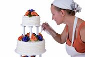 stock photo of cake stand  - baker lady giving to a wedding cake latest small retouches cake has fondant ruffles on the side and decorated with orange and purple gum paste roses - JPG