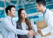 stock photo of handshake  - Family doctor handshaking a couple at the hospital - JPG