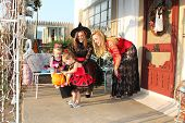 Little girls and their mothers check out candy after trick-or-treating