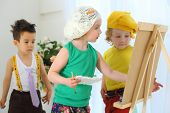 Small children draw pictures on an easel