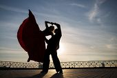 Silhouette of a beautiful young couple dancing on the street against the sky with clouds