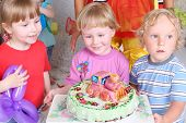 Three happy kids and birthday cake with locomotive at funny children party.