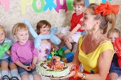 Woman holds birthday cake for little five kids at children party. Inscription Happy Birthday on wall.
