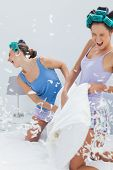 stock photo of slumber party  - Girls having pillow fight at slumber party - JPG