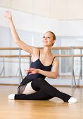 Ballet dancer works out sitting on the floor in the classroom with barre and mirrors