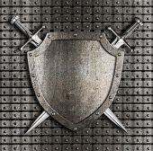 Shield and two swords crossed hanging on metal wall with rivets