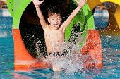stock photo of bathing  - Boy has into pool after going down water slide during summer - JPG