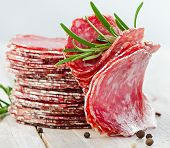 image of salami  - Slices of salami with fresh herbs  - JPG