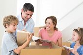 Family of four unpacking cardboard box in new house