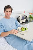 stock photo of hospital gown  - Portrait of man in gown having mean on hospital bed - JPG