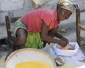 SAINT MARC, HAITI - FEBRUARY 22, 2013.  A woman vendor looking up as she ties a bag of grain she's s