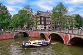 AMSTERDAM, NETHERLANDS - JULY16, 2007: Boat on canal passing by bridges and houses. Small boat trips on city canals is very popular and demanded way to explore city with tourists visiting Amsterdam.