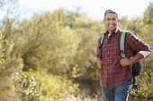 Portrait Of Man Hiking In Countryside Wearing Backpack