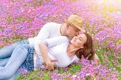Beautiful cheerful couple lying down on floral glade and kissing, romantic date in spring park, youn