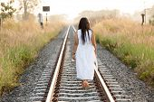 Young woman walking away from the camera down a rural railway track bordered by long grass in a white dress on a summer evening