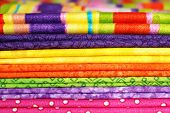 Textile background.  Macro of folded cotton fabrics in bright colors. Swatches in coordinated colors